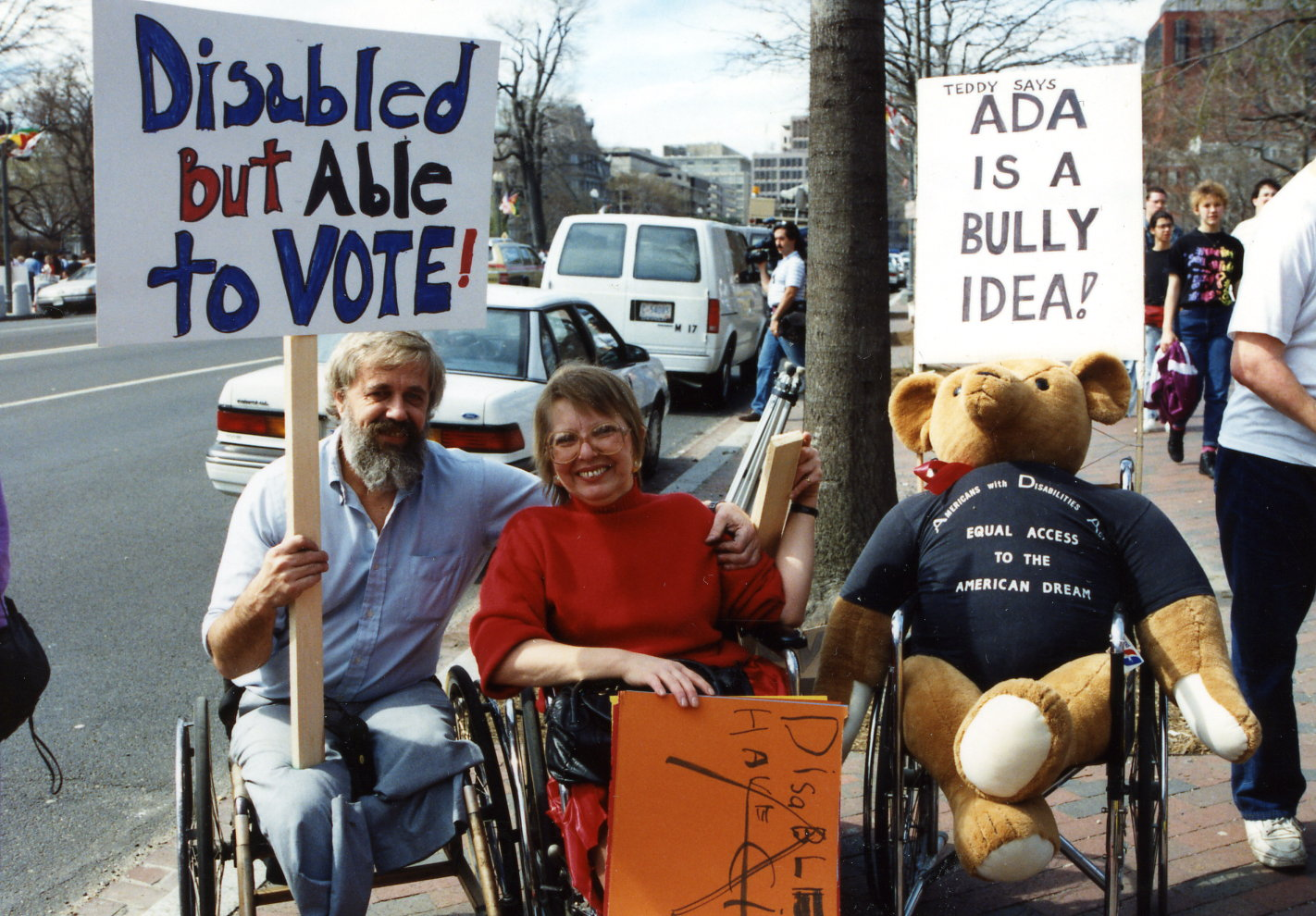 Sharon and her partner, Phil Calkins, and a teddy bear in a wheelchair waiting before marching to the US Capitol