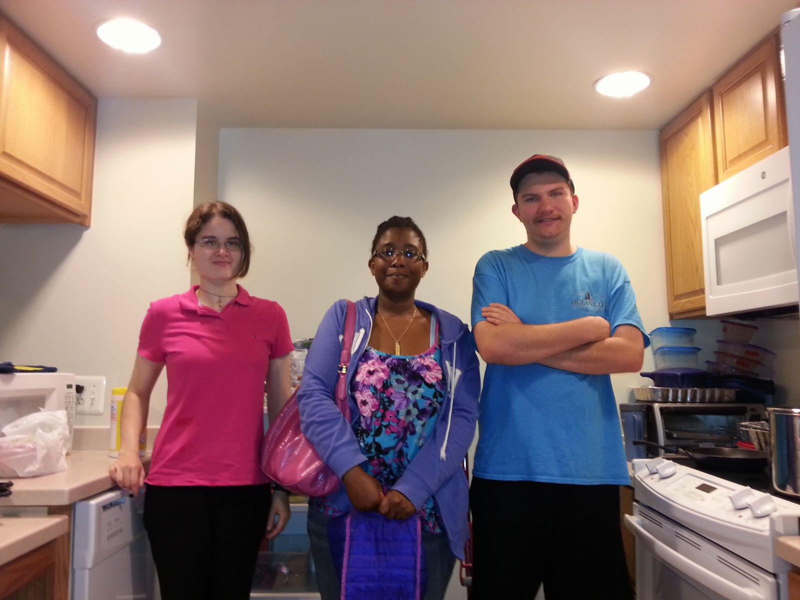 Three youth participants smile standing in the kitchen